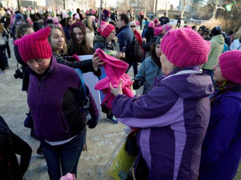 Unas mujeres reparten gorros rosas al inicio de la marcha.
