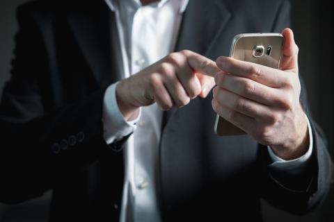 Trabajador con traje y móvil replanteando qué tarifa de datos es la que más le conviene