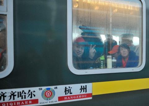 Dos pasajeros de tren saludan a la cámara desde su vagón durante las migraciones masivas por el Año Nuevo Chino 2018.