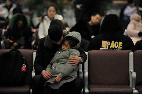 Un hombre y su hija esperan sentados en una estación durante las migraciones masivas por el Año Nuevo Chino 2018.