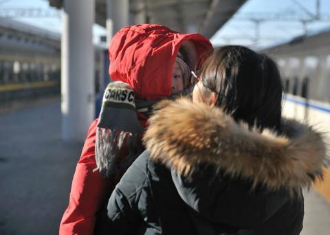 Una mujer abriga a su hijo debido a las bajas temperaturas durante las migraciones masivas por el Año Nuevo Chino 2018.