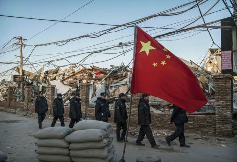 La policía china marcha en formación alrededor de edificios demolidos por las autoridades.
