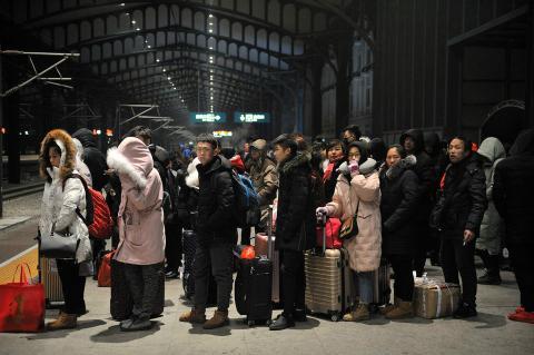 Un grupo de personas esperando en el andén a que llegue su tren durante los desplazamientos por el Año Nuevo Chino 2018.