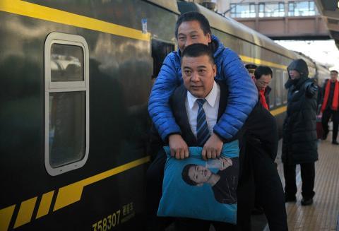 Un conductor de tren se ofrece para transportar a hombros a un señor lesionado durante las migraciones masivas por el Año Nuevo Chino 2018.