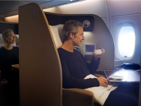 Una persona toma un café en un vuelo en primera clase