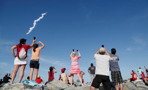 Espectadores en Cocoa Beach observan el primer lanzamiento del cohete Falcon Heavy de SpaceX desde el Centro Espacial Kennedy el pasado 6 de febrero de 2018.