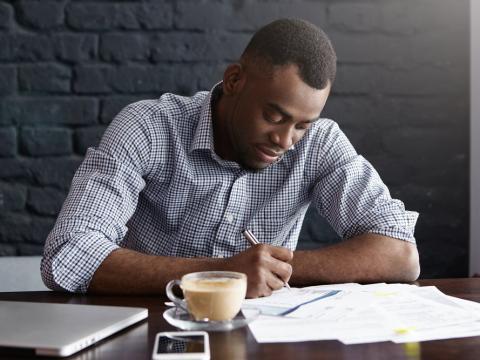 Hombre escribe en una cafetería