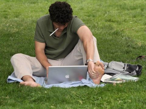 Hombre trabaja con un portátil en un parque