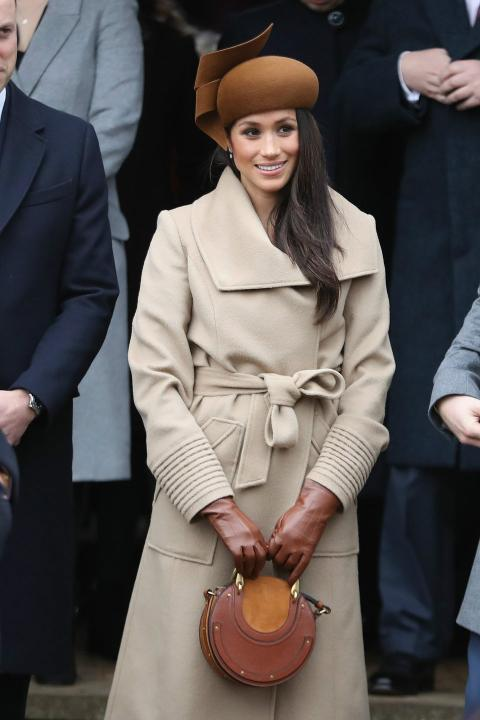 Meghan Markle combina su original sombrero marrón inspirado en los 60s con su bolso de mano.