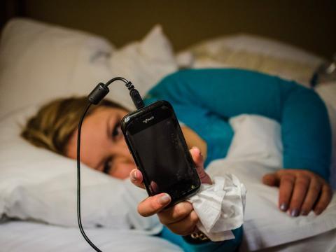 Una mujer mira el móvil mientras está tumbada en la cama.
