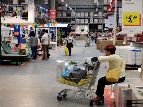 Una mujer espera con un carrito en una tienda de Ikea
