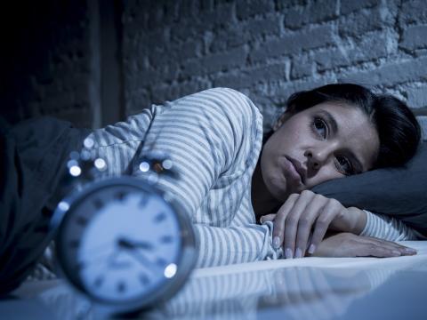 Mujer con insomnio en la cama intentando dormir