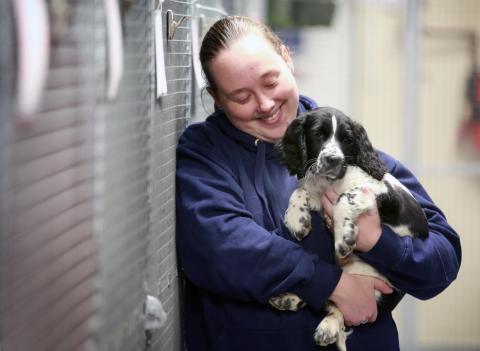 La cuidadora de animales en el aeropuerto de Gatwick sujeta a un cachorro