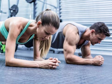 Un chico y una chica realizan flexiones.