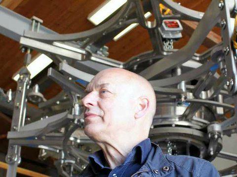 Brian Eno supervisa los mecanismos del reloj gigante apoyado por Jeff Bezos dentro de una montaña