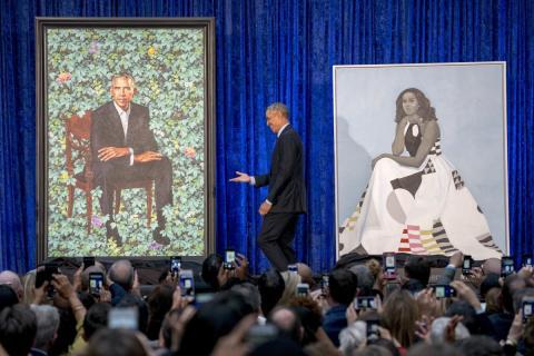 Obama junto su retrato y el de su mujer.
