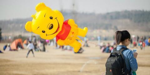 Una niña china sujeta un globo con la forma de Winnie de Pooh.