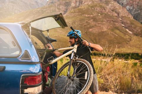 Ciclista intentando meter la bicicleta en el maletero