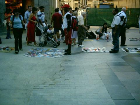 Compradores y vendedores top manta en una calle de una ciudad española.