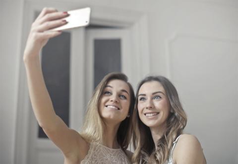 Dos chicas haciéndose un selfie con el móvil