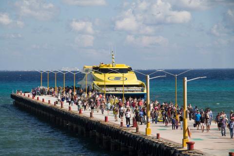 Tristas y pasajeros desembarcan de un ferry que llega a Playa del Carmen, México, el 2 de marzo de 2018.
