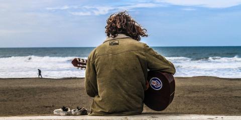 Hombre toca la guitarra en la playa
