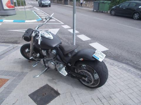 Una moto aparcada en la acera en una calle de Madrid