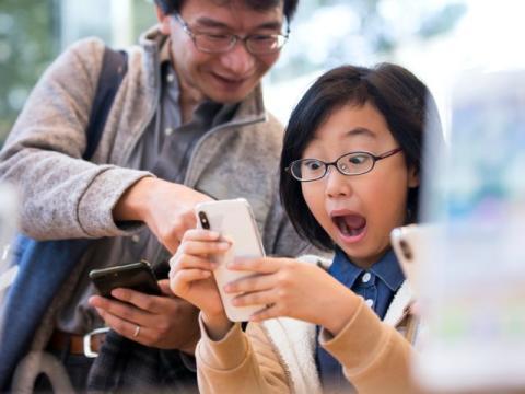 mujer asiática sorprendida usando un smarphone junto a un hombre