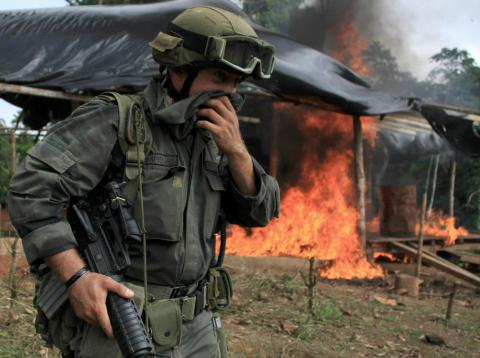 Un miembro de una brigada antinarcóticos frente a una cabaña en llamas durante una redada para destruir un laboratorio de coca cerca de Tumaco, región situada en el sur de Colombia, el 8 de junio de 2008.