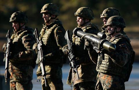 Los soldados de la Bundeswehr presentan sus armas durante los ejercicios militares anuales en los campos de entrenamiento militar de Bergen el 2 de octubre de 2013.
