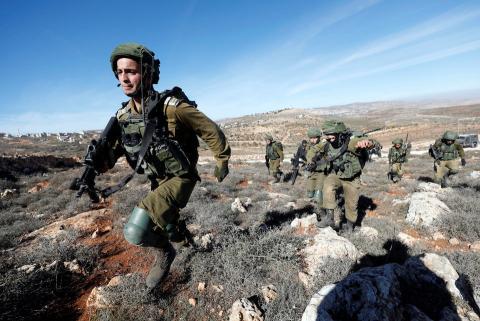 Soldados israelíes corren hacia los palestinos durante los enfrentamientos en la aldea de Qusrah, en Cisjordania, el 4 de diciembre de 2017.