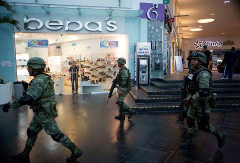 Soldados en el interior del centro comercial Plaza Las Américas después de un tiroteo en Cancún, el 17 de enero de 2017. Hombres armados atacaron la oficina del fiscal días después de un tiroteo mortal en un festival de música.