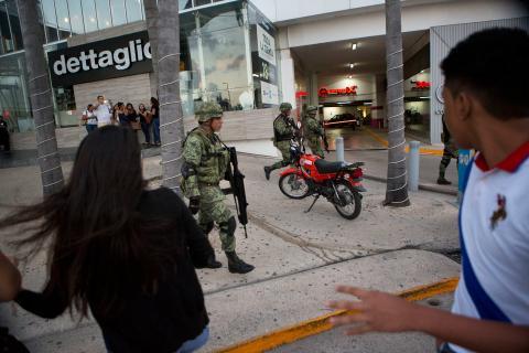 La gente reacciona con ansia a las patrullas de soldados dentro del centro comercial de la Plaza de las Américas, en Cancún.