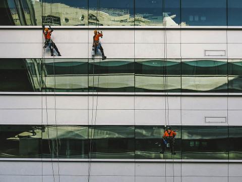 Trabajadores colgados de la pared de un edificio