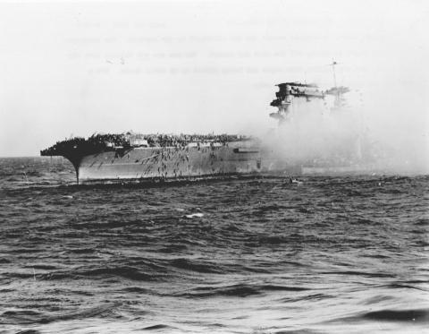 La tripulación superviviente del USS Lexington, hundida por los japoneses en el Mar de Coral, abandona el barco. Los marineros se deslizan por las cuerdas y son recogidos por pequeños botes. El destructor, a la derecha, recoge a los enfermos y heridos.
