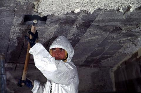 A worker removes asbestos cement from the ceiling of a primary school in France.