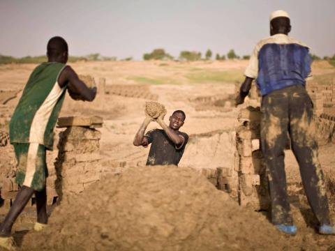 Los trabajadores trabajan la tierra para convertirla en ladrillos en una fábrica ribereña donde se cuece barro en hornos para producir materiales de construcción en las afueras de la capital de Chad.