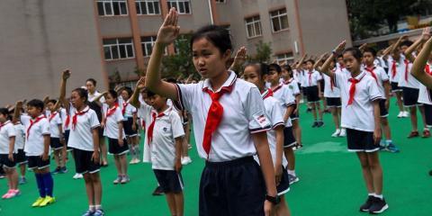 Unos estudiantes cantan el himno nacional en el patio de recreo durante la jura de bandera en una escuela de Shanghai el 27 de septiembre de 2017.