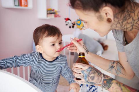 Madre dando el jarabe a su hijo