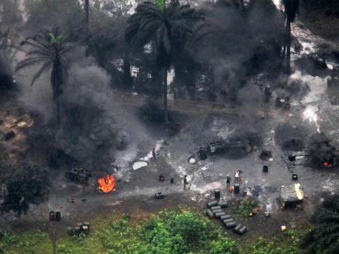 Humo elevándose desde una refinería ilegal de petróleo crudo en una comunidad ogoni.