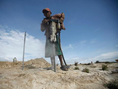 A boy with a pneumatic drill breaks rocks near a construction site in Myanmar.
