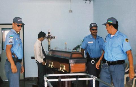 Agentes de seguridad alrededor del ataúd de la leyenda de la navegación Peter Blake antes de ser embarcados en un avión de la fuerza aérea brasileña en Macapa, el 9 de diciembre de 2001. Blake fue asesinado por piratas el 6 de diciembre de 2001.