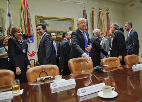President Donald Trump tosses his folder on the table before the start of a meeting with automobile leaders.