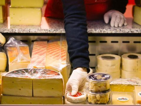 Un dependiente coge queso de un mostrador