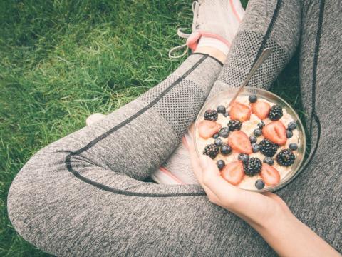 Una deportista con un tazón de fruta y avena.