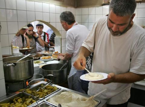 Shmulik Nahmias prepares to serve a plate at Rahmo, his legendary hummus restaurant in Jerusalem's Mahane Yehuda market.