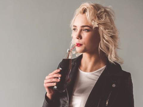 Una mujer bebe una bebida azucarada