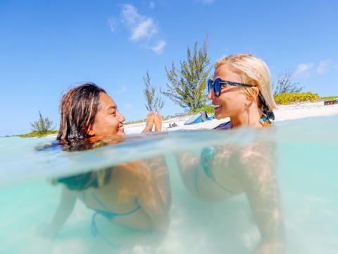 Roth y una compañera SuperShe toman el sol en las aguas de las Islas Turcas y Caicos, que originalmente iba a ser la sede de la comunidad.