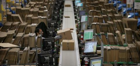 Un trabajador de Amazon coloca un paquete en una cinta