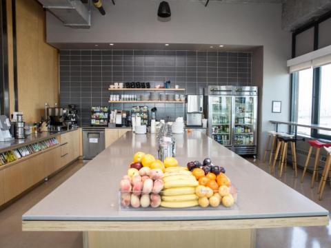 Si su oficina cuenta con refrigerios, como en la fotografía de la oficina de Dos Sigma, camine hacia la cocina para reabastecerse de combustible. Es una buena excusa para moverte.